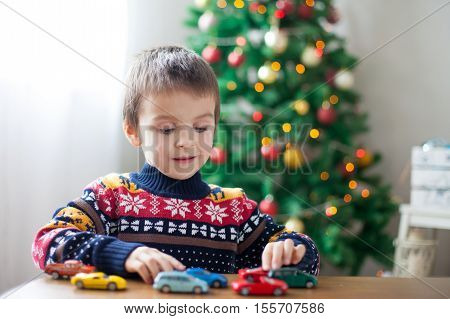 Adorable Little Preschool Boy, Playing With Toy Cars At Home On Christmas