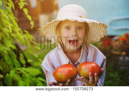Little happy girl with tomato in the hands of
