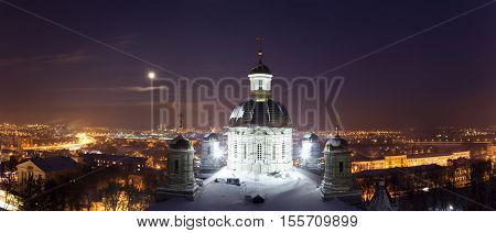 Night winter panorama of the Penza city in a full moon with illuminated orthodox cathedral on the foreground and residential areas and highway a top view Russia
