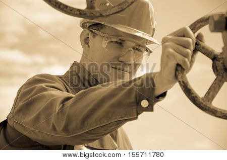 Oilfield worker near wellhead valve wearing helmet. Oil and gas concept. Toned.