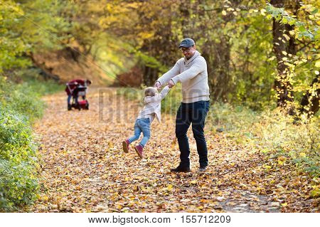 Beautiful young family on a walk in forest. Father spinning his little daughter and mother with her son in pushchair outside in colorful autumn nature.