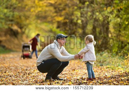 Beautiful young family on a walk in forest. Father playing with his daughter and mother with her son in pushchair outside in colorful autumn nature.