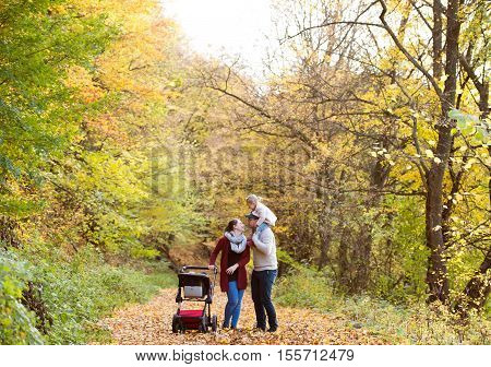 Beautiful young family on a walk in forest. Father giving his daughter piggyback and mother with her son in pushchair outside in colorful autumn nature.