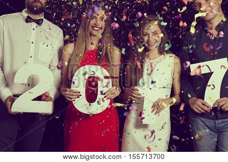 Four friends having fun at New Year's Eve Party holding cardboard numbers 2017 at midnight countdown