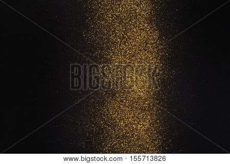 Golden glitter sand texture stripe on black, abstract background with copy space. Yellow dusty shimmer decoration line, shiny and sparkling. Holidays and glamour concept.