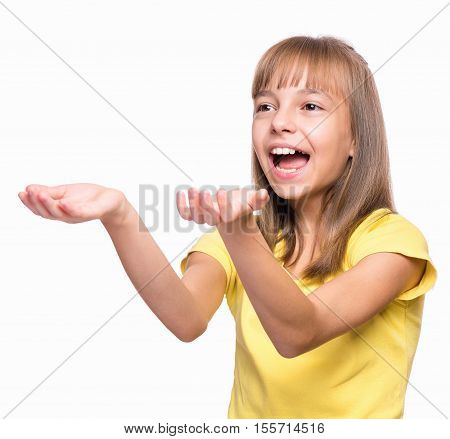 Happy cute child reaching out her palms and catching something. Half-length emotional portrait of caucasian little girl wearing yellow t-shirt, surprised. Funny kid trying to catch something, isolated on white background.