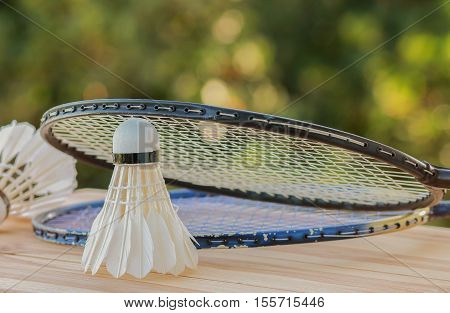 shuttlecocks on racket for a badminton on wood background light green outdoor background