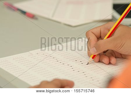 Thai student testing in exercise exams answer sheets with pencil