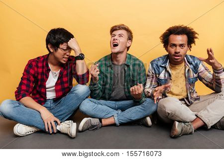 Three mad furious young men friends sitting and shouting over yellow background