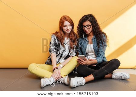 Two smiling beautiful young women with earphones listening to music from smartphone