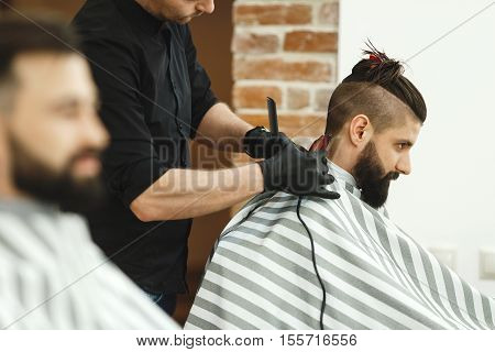 Attractive dark haired man wearing black shirt doing a haircut for man with long black hair at barber shop, copy space.