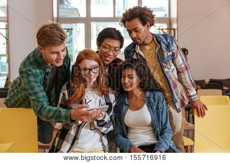 Multiethnic group of young people sitting and using mobile phone together