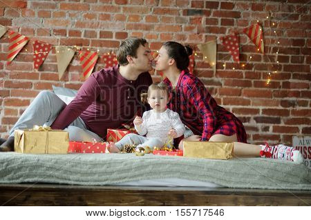 Christmas morning. The young family gleefully congratulates each other Marry Christmas. On a bed there are many Christmas gifts in bright packings. Merry Christmas and a Happy New Year.