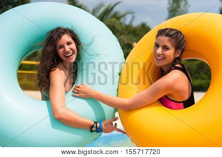 Happy young two women in bikini with rubber inflatable float, playing and having a good time at water fun park pool, on a summer hot day