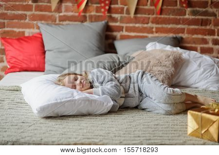 Little girl in a soft pajamas has fallen asleep. She sleeps on a big cozy bed with a set of pillows. On the edge of a bed the gold box with a gift lies. The brick wall is decorated by a holiday.