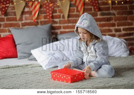 Christmas morning. The little girl in a soft pajamas sits on a big bed and angrily looks at a bright red box. The girl is disappointed with the Christmas gift. She expected other gift by Christmas.