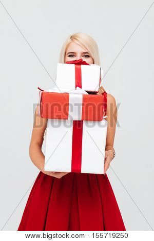Happy blonde woman in red dress peeking out from stack of xmas presents isolated on the white background