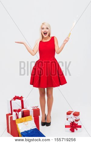 Excited cheerful woman in red dress holding flapper and having fun