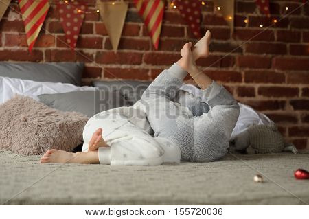 Christmas morning. Two children have put up a cheerful fight on a big bed. They flounder among soft pillows. Brick wall is decorated with Christmas garlands. Children adore Christmas.