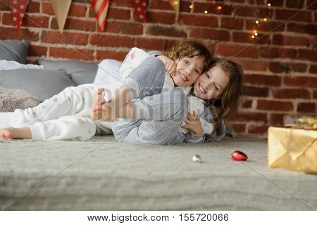 Christmas morning. Brother and sister have put up cheerful fight on big bed. Brick wall is decorated with Christmas garlands. On the edge of a bed there is a Christmas gift. Children adore Christmas.