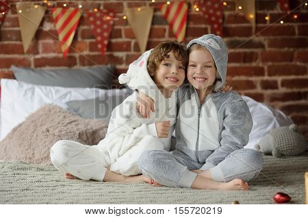 Christmas. Two children in pajamas sitting on the bed waiting for Christmas gifts. The bedroom is decorated with festive garlands. Children happily embrace. Merry Christmas. Happy Christmas.