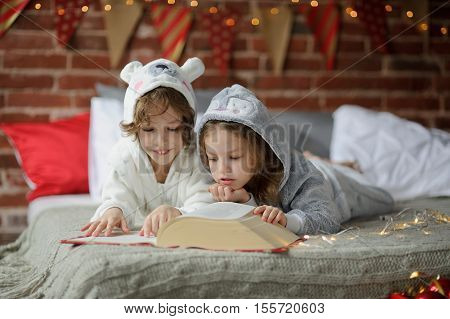 Christmas Holidays. Two children lay on a bed in soft pyjamas. Bedroom is decorated by christmas garlands. The children read a great book with Christmas tales. Christmas - magic time. Merry Christmas.