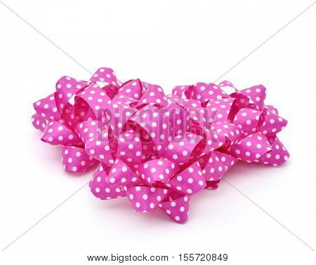some gift puff bows made with pink ribbon patterned with white dots, on a white background