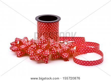 some gift puff bows made with red ribbon patterned with white dots and a roll of this ribbon, on a white background