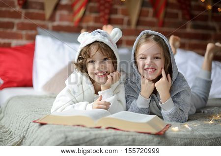 Christmas Holidays. Two children brother and sister lie on big bed and read Christmas tales. Children dressed in fluffy pajamas like little cute animals. Before them the huge book. Magic Christmas.