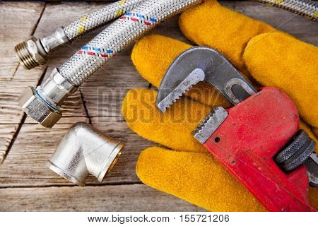 Set of plumbing and tools on the table. Fitting, suede gloves and adjustable wrench for plumbing works