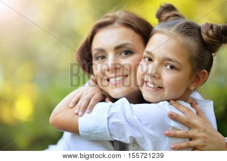 Lifestyle portrait of mother and daughter in happines at the outside in the meadow