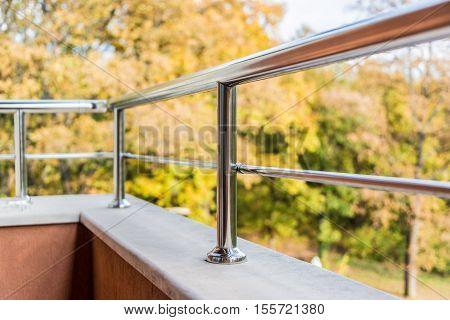 Close up of a balcony metal balustrade. Autumn view in the background.
