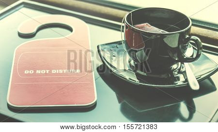 Do not disturb sign and a cup of tea over a dark tray by the window. Time for rest concept.