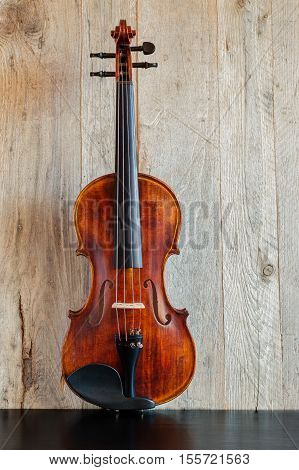 Standard violin made of wood in upright position on a black wooden table