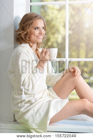 full lenght portrait of young beautiful woman with a cup of tea sitting on windowsill