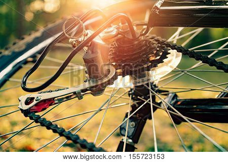 Close up of a Bicycle wheel with details, chain and gearshift mechanism, in morning sunlight.
