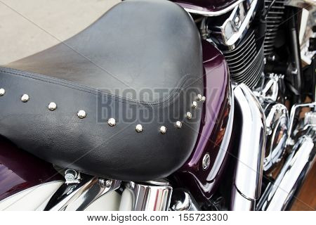 Purple motorcycle with vintage, leather seat. Close-up seat and wheel of bike. Traveling concept.