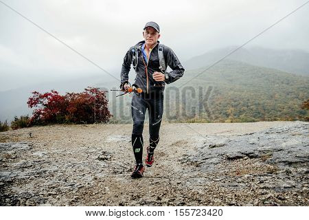 Yalta Russia - October 8 2016: runner middle-aged men running in rain on a mountain trail with walking poles during Crimea mountain marathon