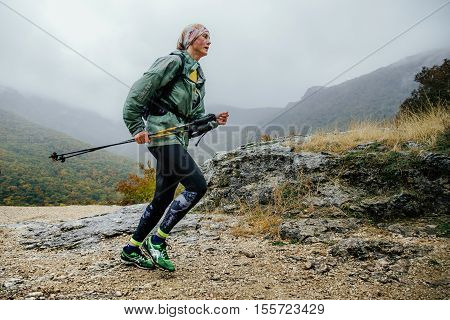 Yalta Russia - October 8 2016: runner middle-aged woman running in rain on a mountain trail with walking poles during Crimea mountain marathon