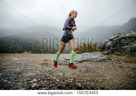 Yalta Russia - October 8 2016: young girl runner running in rain in compression socks and running backpack during Crimea mountain marathon