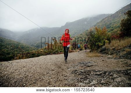 Yalta Russia - October 8 2016: young girl runner running in rain in a red jacket with a smile on face during Crimea mountain marathon