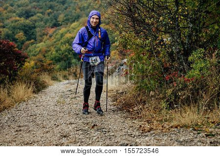 Yalta Russia - October 8 2016: young man with walking poles running in rainy weather on mountain trail during Crimea mountain marathon