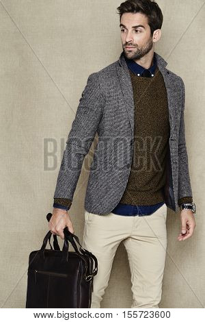fashionable bussines Man holding bag in studio