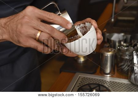 expert barista close up hands preparing delicious coffee cream pouring milk in mug decorating with foam at coffee shop restaurant in cafe preparation concept