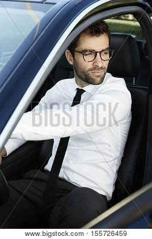 Businessman sitting in driving seat looking away