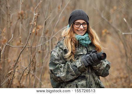 Young Beautiful Woman In Camouflage Outfit Discovering Nature In The Forest With Photo Camera. Trave