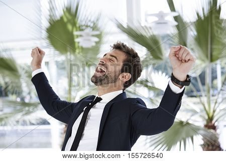 Cheering businessman in smart suit joyful over succes