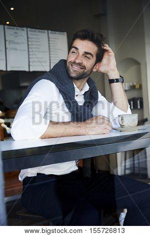 Guy taking a break in cafe smiling