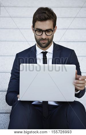 handsome young Businessman using laptop on staircase