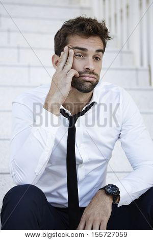 Morose businessman sitting on steps looking away